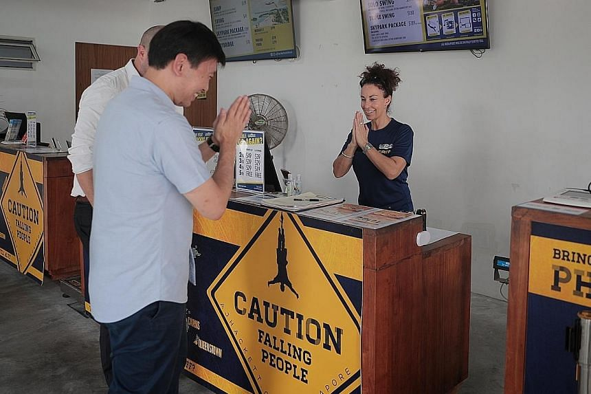 Senior Minister of State for Trade and Industry Chee Hong Tat greeting a staff member at bungee jump attraction AJ Hackett during a visit to Sentosa yesterday. AJ Hackett has seen a 50 per cent drop in customers in recent weeks.