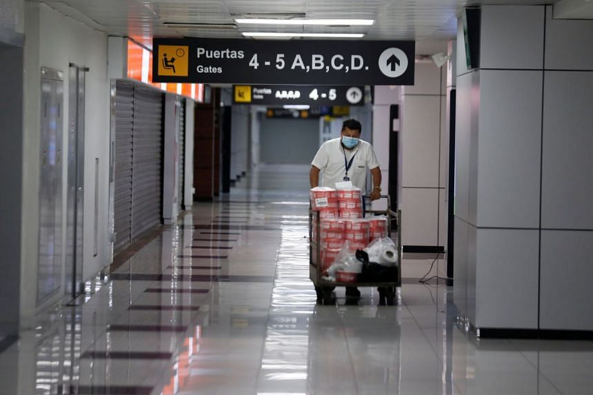 An airport worker wears a protective face mask at the El Salvador International Airport Saint Oscar Romero y Galdamez, on March 8, 2020.