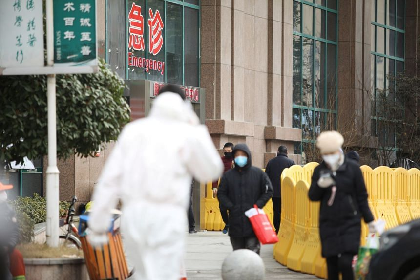 In a photo taken on Feb 7, 2020, people wearing face masks walk outside the Central Hospital of Wuhan.