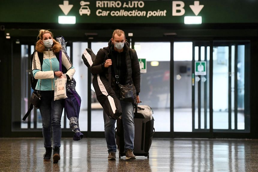 People wearing protective masks walk in Malpensa airport near Milan, Italy, on March 9, 2020.