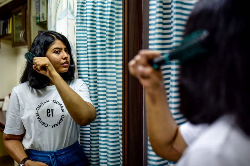 Ms Shreya Siddanagowder brushing her hair in a bathroom at her home in Pune  on March 7, 2020, more than two years after her transplant surgery.