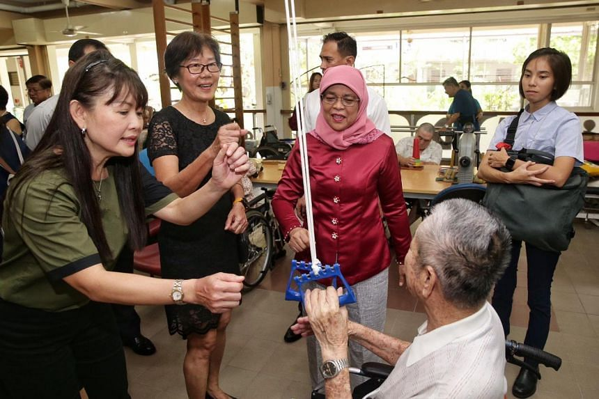 (From left) Ling Kwang Home for Senior Citizens' daycare centre executive Annie Heng and director of nursing Lee Geok Yian, and President Halimah Yacob interacting with a client under the Integrated Home and Day Care programme on March 12, 2020.