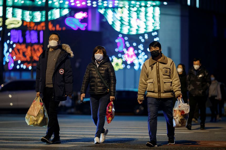 People wear face masks outside a shopping mall in Beijing on March 11, 2020.