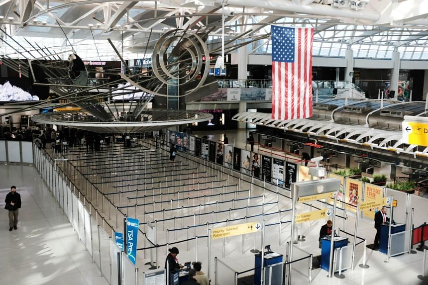 People walk through an empty international departure terminal at New York's John F. Kennedy Airport as concern over the coronavirus grows on March 7, 2020.