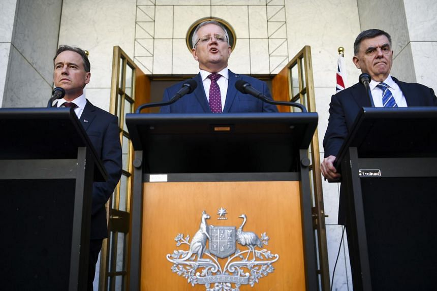 (From left) Australian Health Minister Greg Hunt, Australian Prime Minister Scott Morrison and Australia's Chief Medical Officer Professor Brendan Murphy speak during a press conference at Parliament House in Canberra on March 11, 2020.