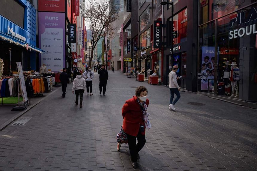 Pedestrians wearing face masks walk through the Myeongdong shopping district of Seoul on March 6, 2020.