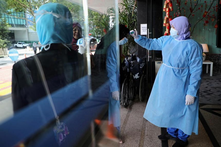 A nurse conducts temperature checks at a hospital in Kuala Lumpur on Feb 3, 2020.