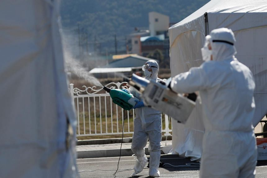 Quarantine workers in protective gear spray disinfectants at a screening facility near Daegu, Korea, on March 11, 2020.