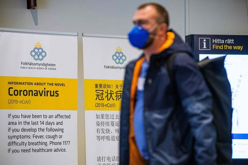 A passenger arriving in Stockholm's Arlanda airport is greeted by signs advising travellers what to do if they show symptoms of infection by the new coronavirus after arriving in Sweden.