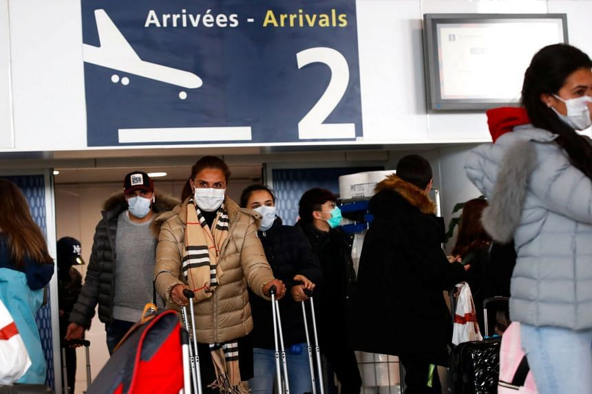 In a photo taken on Feb 29, 2020, people wearing protective face masks arrive at Charles de Gaulle airport in Paris, France.