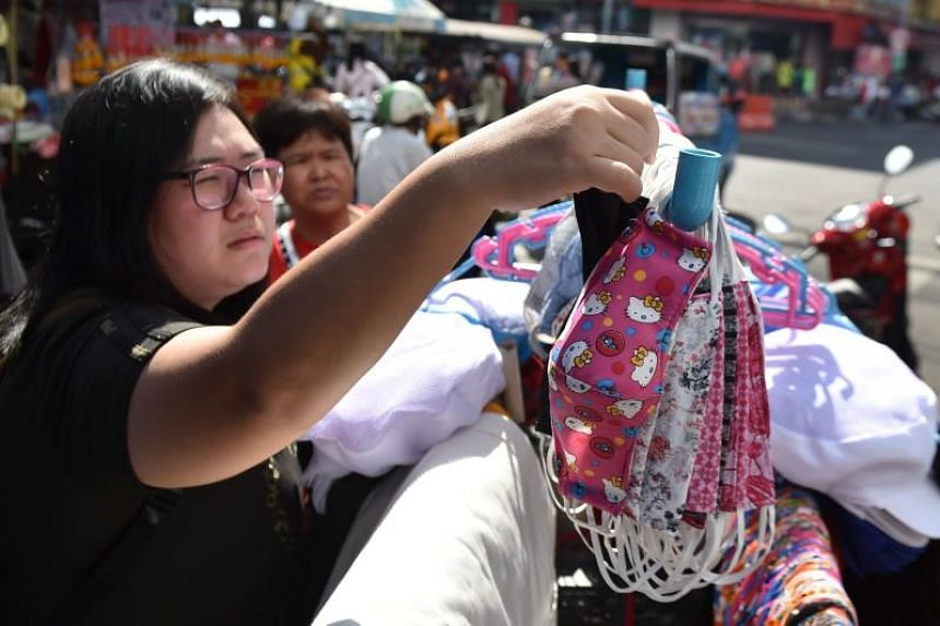 A woman chooses a cloth face mask in the Kim Yong market in Hadyai district in Thailand's southern of Songkhla province, on Jan 26, 2020.