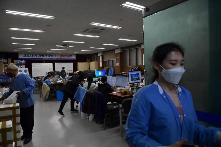 In a photo taken on March 10, 2020, hospital workers track responses to the Covid-19 novel coronavirus at a situation room at a hospital in Daegu.