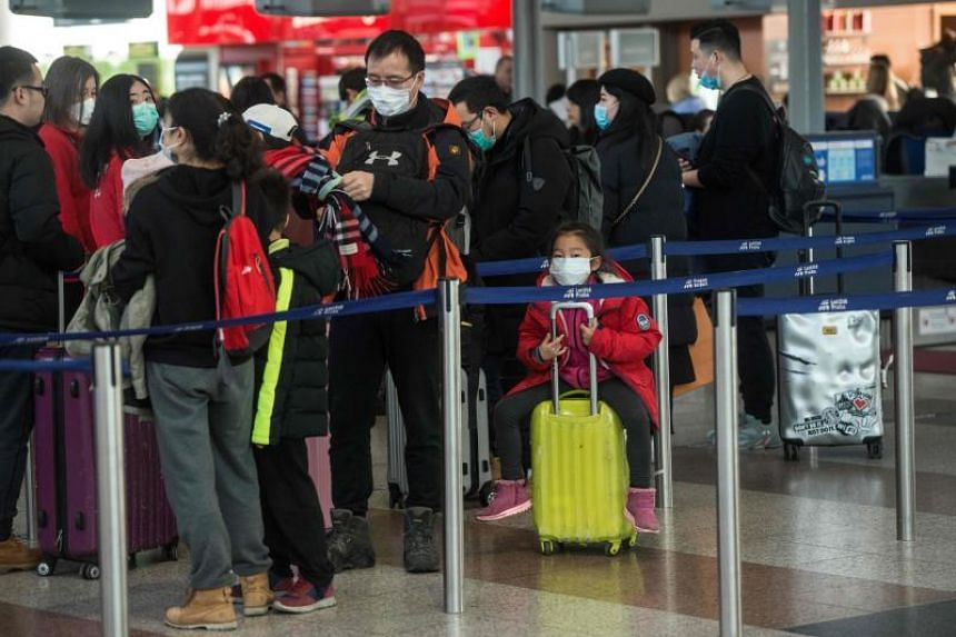 A photo taken on Jan 27, 2020 shows travellers and staff members with masks at the checking area for flights at the Vaclav Havel International Airport in Prague.