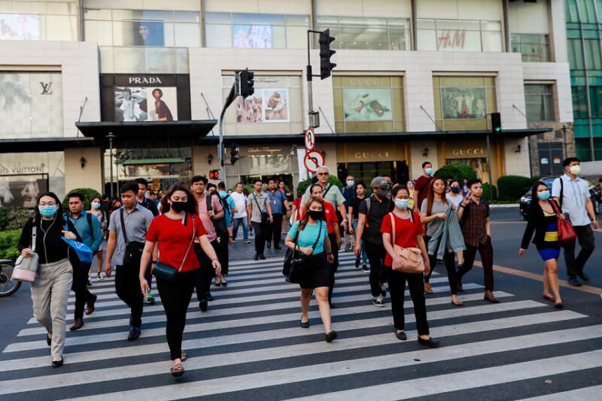 In a photo taken on March 11, 2020, pedestrians with protective face masks cross a street outside a shopping mall in Manila.