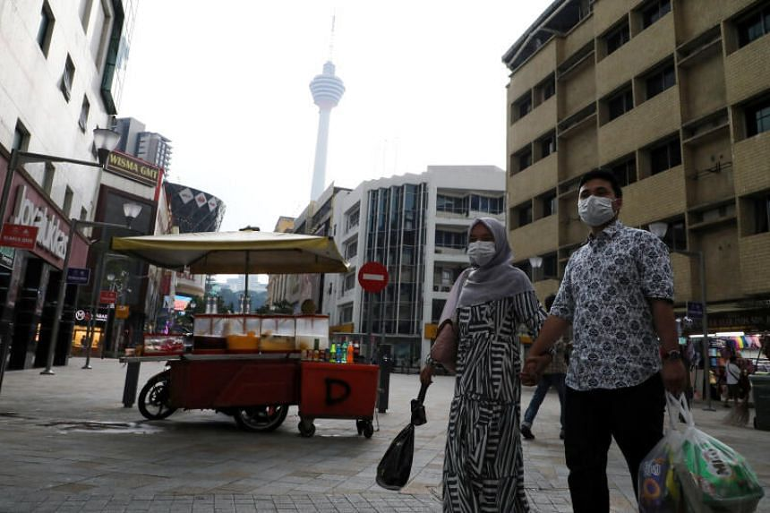 A couple wearing protective face masks cross a street, following the outbreak of the coronavirus in Kuala Lumpur, on March 6, 2020.