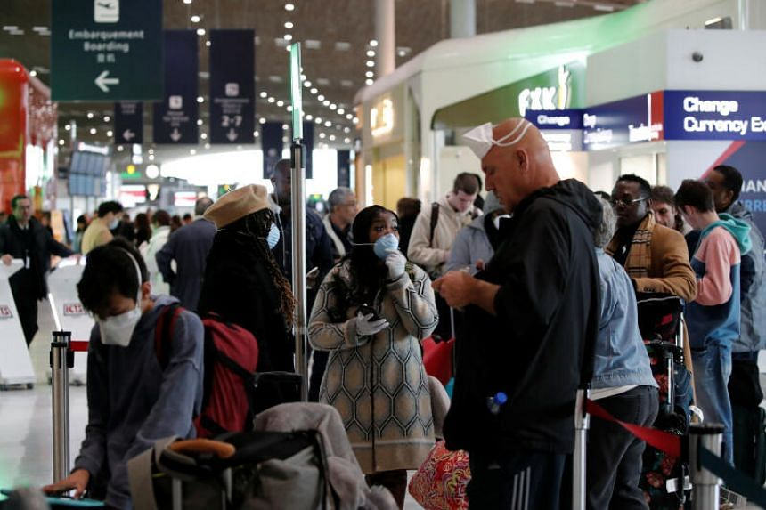 Travellers wearing protective face masks line up at the Delta Air Lines ticketing desk inside Terminal 2E at Paris' Charles de Gaulle airport, after the US banned travel from Europe over the coronavirus outbreak, on March 12, 2020.