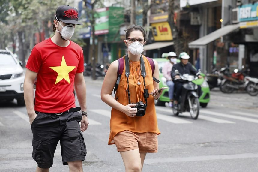 Foreign tourists wearing face masks walk in Hanoi, Vietnam, March 12, 2020.