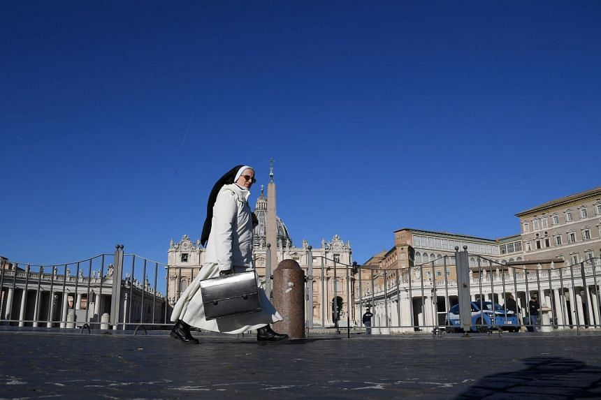 A nun walks next to an empty St Peter's Square, on the third day of an unprecedented lockdown across of all Italy imposed to slow the outbreak of coronavirus.