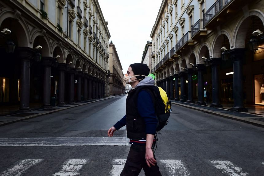 A person walks in a virtually deserted Via Roma, on the third day of an unprecedented lockdown across Italy.