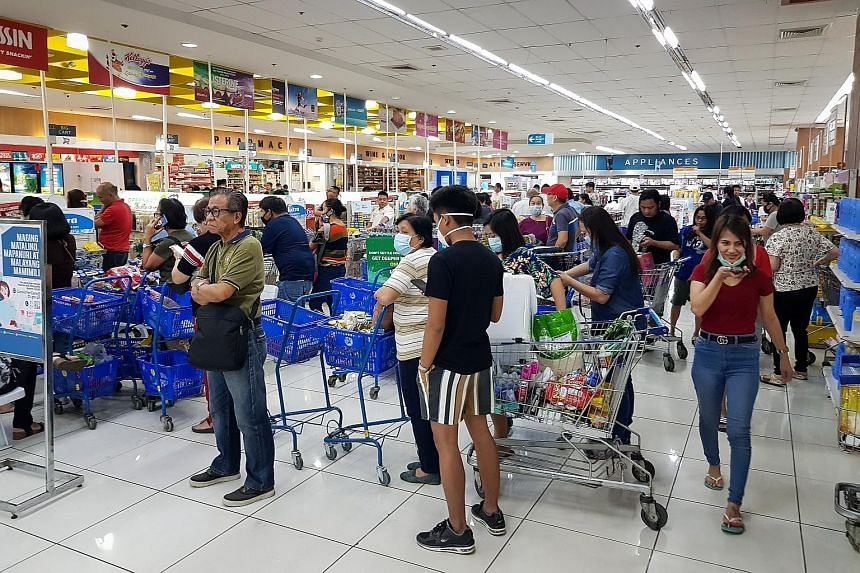 Shoppers endured long queues at checkout counters in groceries and supermarkets in Manila yesterday as word that a lockdown would be enforced set off panic buying across Metro Manila. Shelves were emptied quickly, with sanitisers, disinfectants, rice