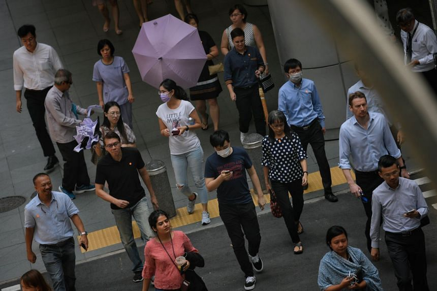 People wear masks as they cross the road in Singapore's Central Business District on March 10, 2020.
