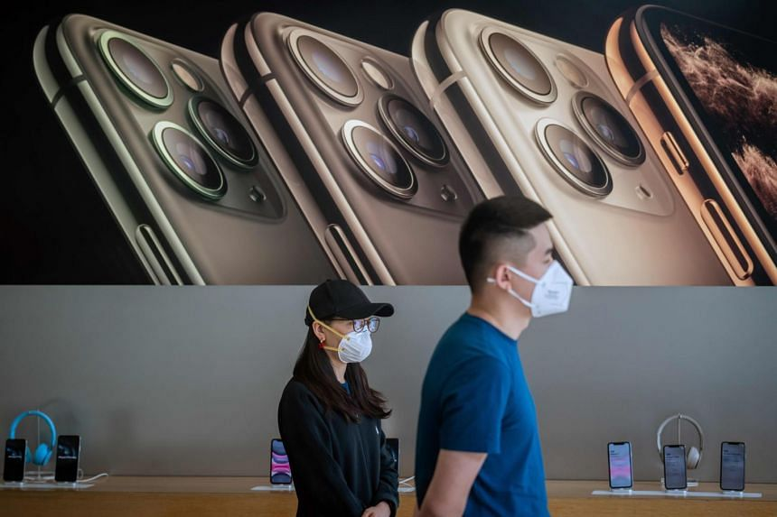 Apple staff wear face masks as a preventive measure at an Apple shop in Beijing on March 11, 2020.