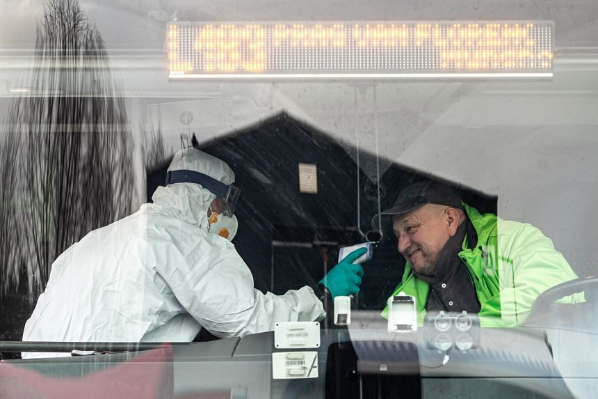 A police officer in a protective suit checks the temperature of a bus driver at the Rozvadov border crossing from the Germany side near city of Rozvadov, Czech Republic, on March 9, 2020.