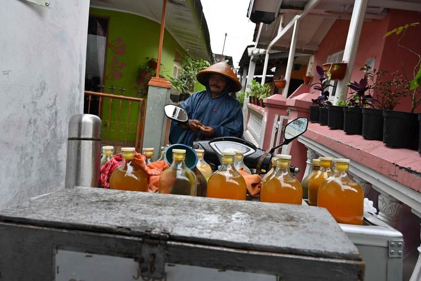 An Indonesian vendor serves jamu, an Indonesian traditional herbal drink, in Jakarta, on March 5, 2020.