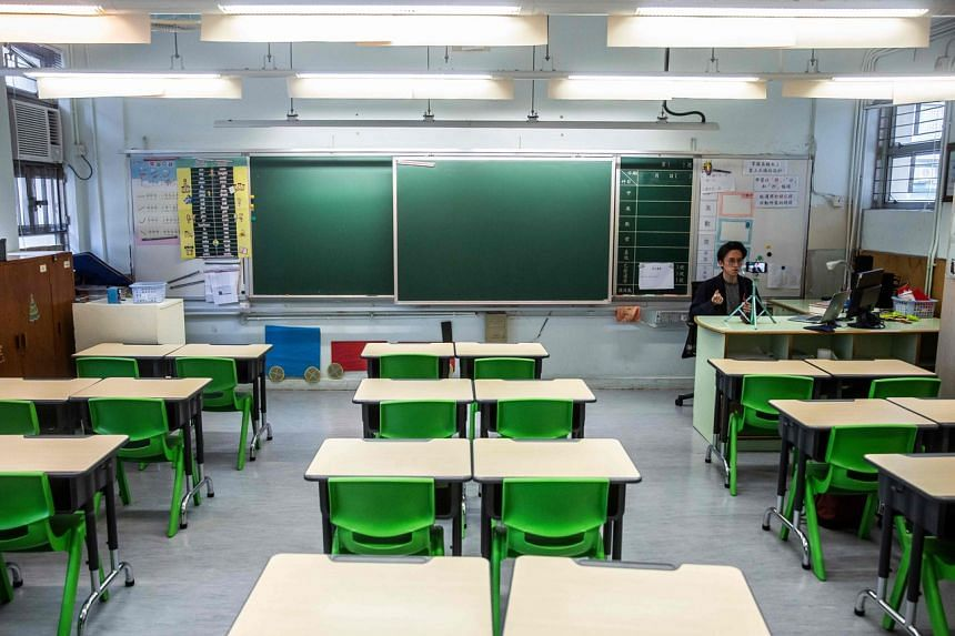 Primary school teacher Billy Yeung recording a video lesson in an empty classroom in Hong Kong on March 6, 2020, for his pupils, who have had their classes suspended due to the coronavirus outbreak.
