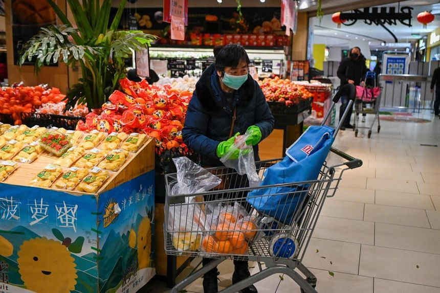 A woman choosing fruit at a supermarket in Beijing on March 12, 2020.