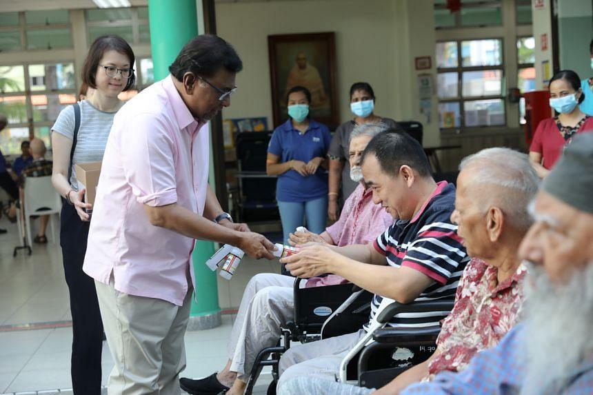 Temasek Foundation chairman Richard Magnus distributing hand sanitiser to Mr Tan Joo Huat and residents at Sree Narayana Nursing Home, on March 13, 2020.