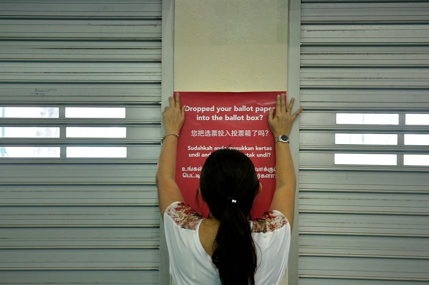 In this file picture taken on Sept 10, 2015, an election officer puts up a poster while setting up the polling station at Pei Chun Public School in Toa Payoh.
