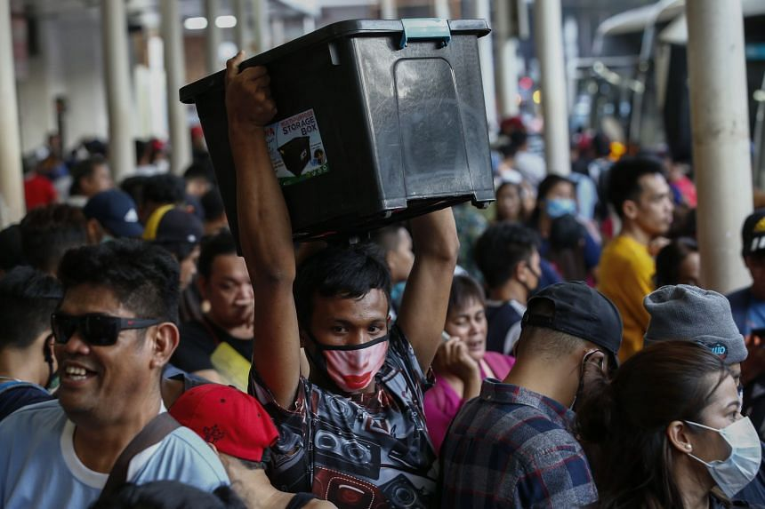 A traveller at the Araneta bus depot carries his belongings through a crowd of other travellers hoping for a bus ride out of the capital region before a community quarantine takes effect.