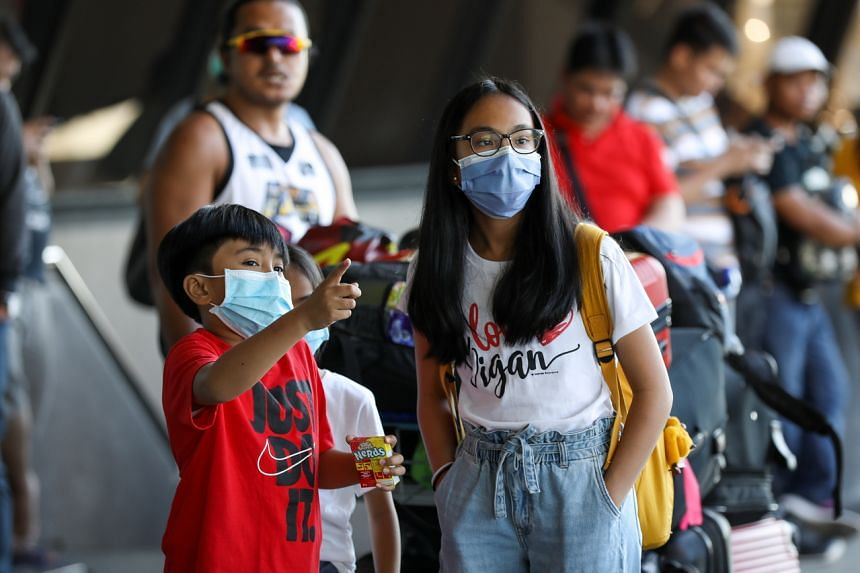 Children wear protective face masks at the Ninoy Aquino International Airport's Terminal 1 in Manila, on March 13, 2020.