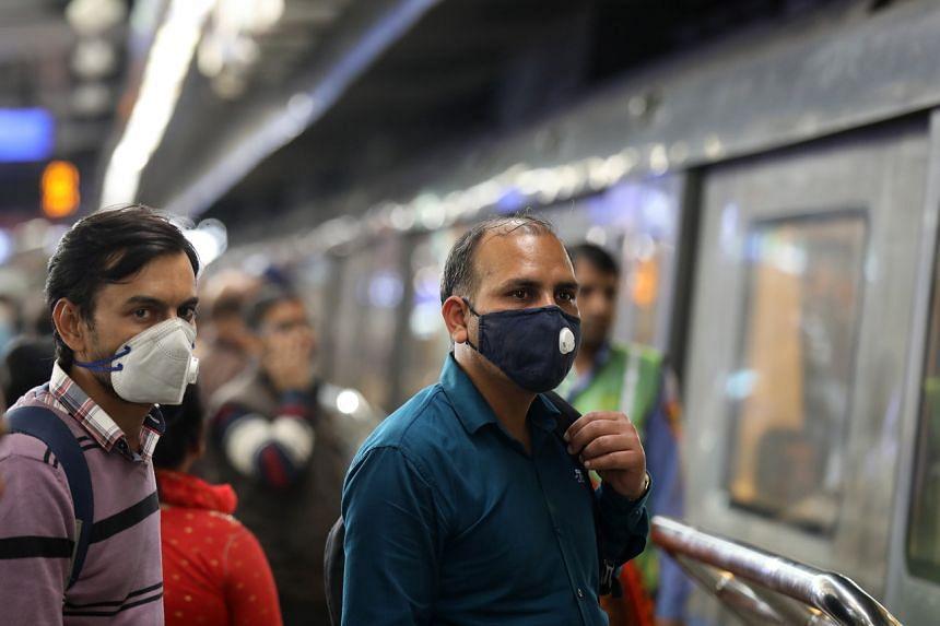 People wear protective masks as the precautionary measure for Covid-19 coronavirus inside Delhi metro in New Delhi, on March 13, 2020.