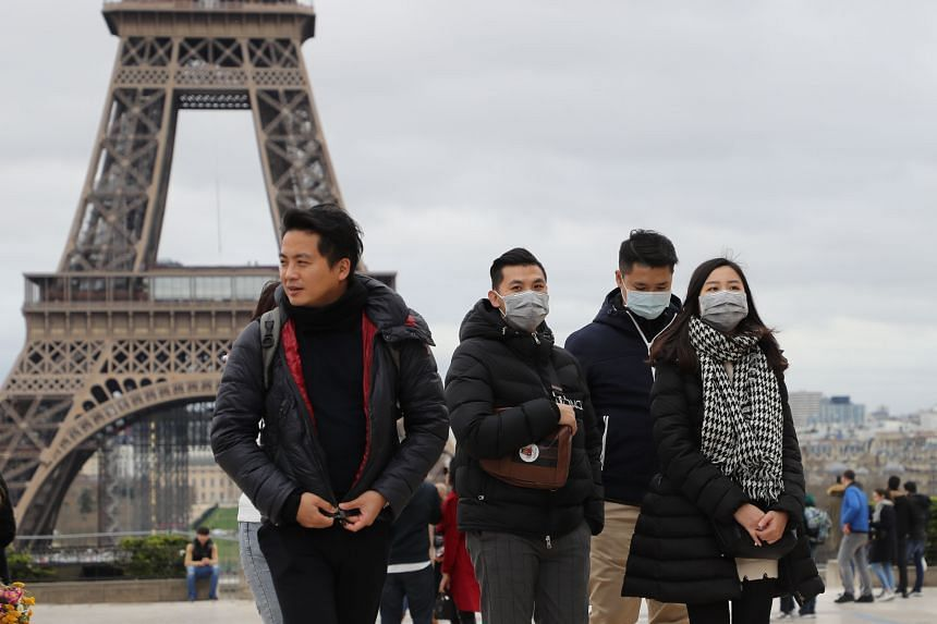 A photo taken on March 10, 2020 shows people with protective face masks near the Eiffel Tower in Paris.