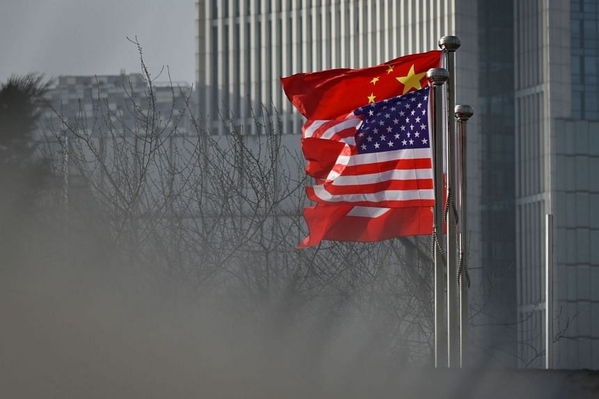 Chinese and US national flags flutter at the entrance of a company office building in Beijing.