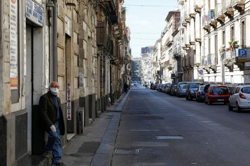 A man stands on an empty street in Catania, Italy, on March 14, 2020.