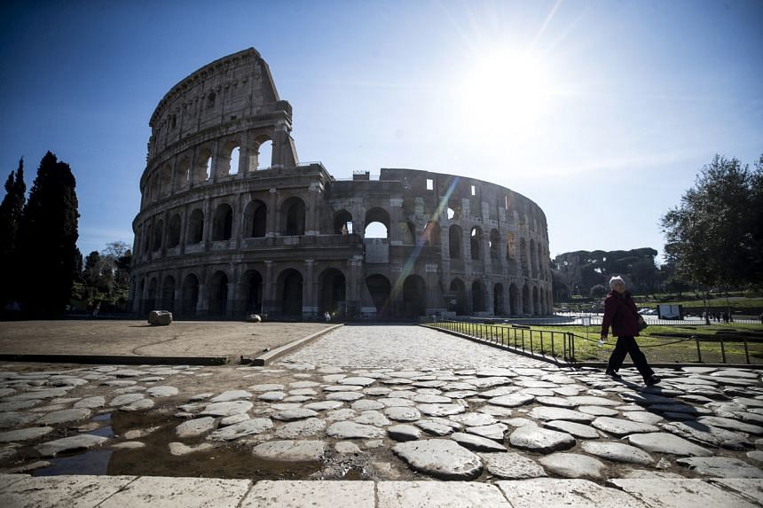 A woman walks near the deserted Colosseum in Rome on March 10, 2020.