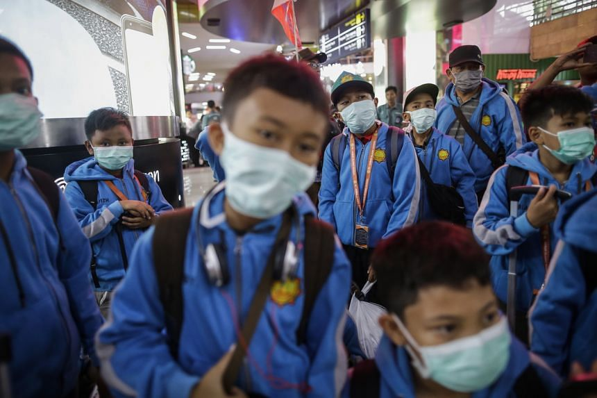 Indonesian students wearing masks at Gambir train station in Jakarta on March 12, 2020. The city is closing all schools starting next week.