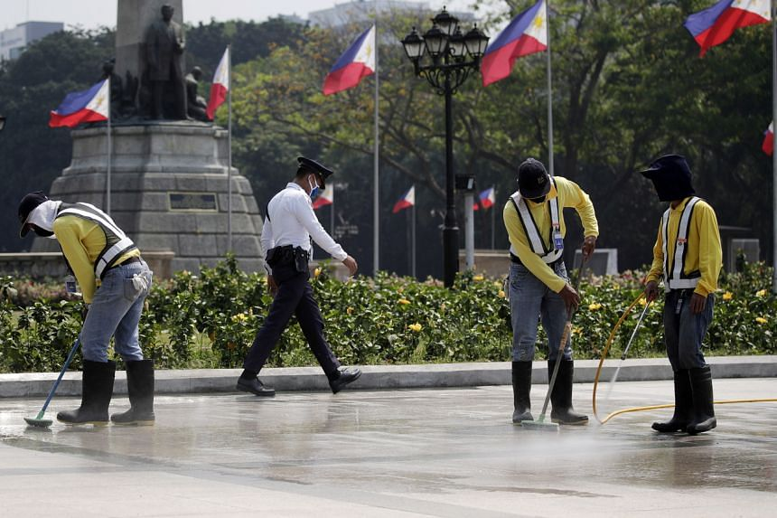 Workers disinfect the surroundings of the monument of Philippine national hero Jose Rizal after it was closed to the public, at the Luneta Park in Manila, on March 14, 2020.