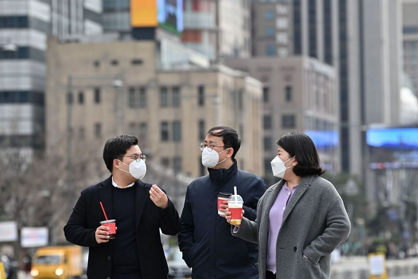 """Pedestrians in Gwanghwamun square in downtown Seoul, on March 12, 2020. Calling in sick is frowned upon in South Korea, where """"good work"""" equals long hours in the office."""