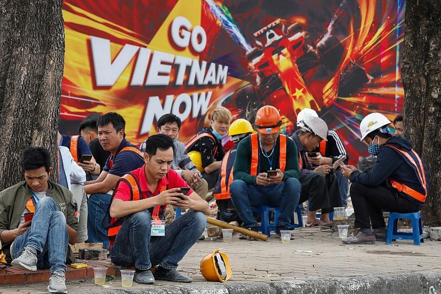 Workers taking a break in front of a poster promoting the Formula One Vietnam Grand Prix at the construction site of its racing track in Hanoi last Thursday. The event has been postponed.