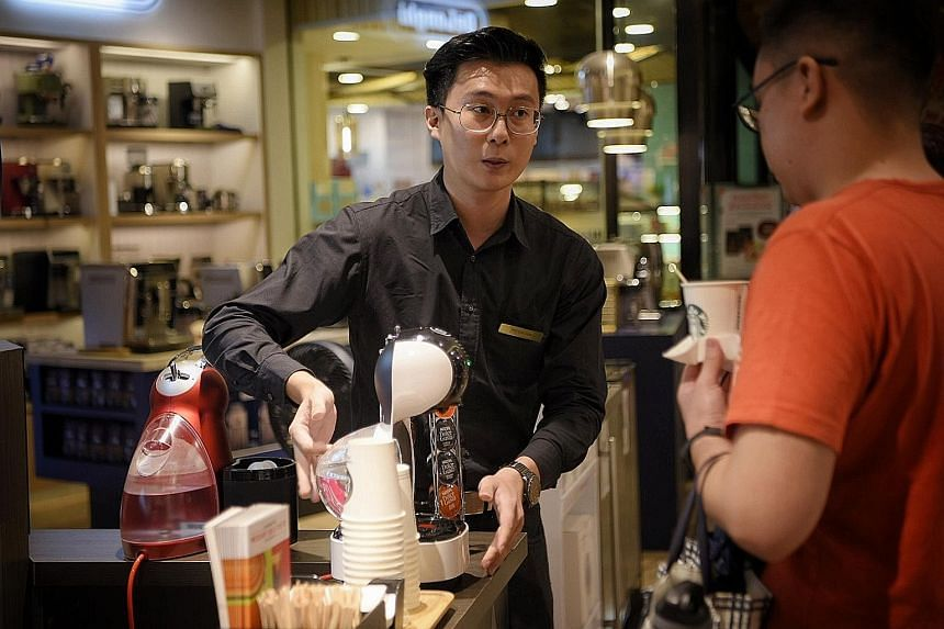 Mr Dylan Teo, a coffee-making machine promoter at Tangs department store, giving out coffee samples.
