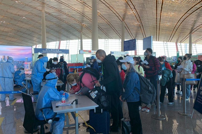 Staff getting information from travellers at Beijing Capital International Airport, on March 14, 2020.