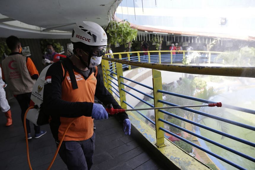 A volunteer spraying disinfectant at a bus station in Jakarta on March 15, 2020.