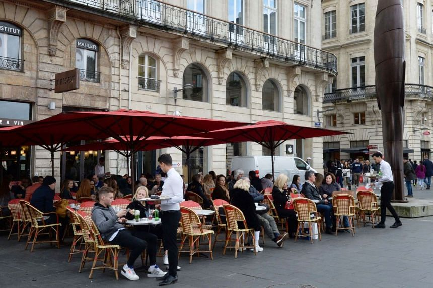 People sit on the terrace of a cafe in Bordeaux on March 14, 2020.