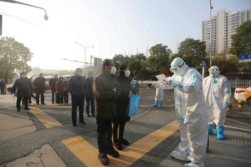 Medical workers check patients who recovered from the coronavirus as they arrive to be tested again at a hospital in Wuhan, China, on March 14, 2020.