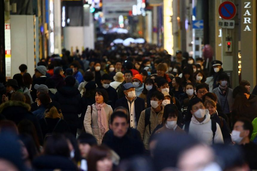 People wearing protective masks walk in the Dotonbori amusement district of Osaka, Japan, on March 14, 2020.
