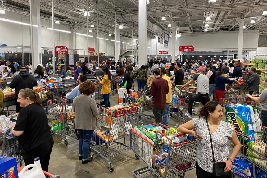 Shoppers line up with full carts in a supermarket in Virginia, on March 13, 2020.